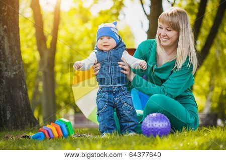 Happy mother and baby on the meadow