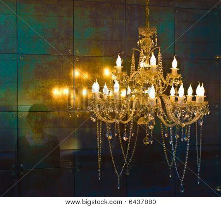 Crystal Chandelier Lighting Near The Mirror Wall