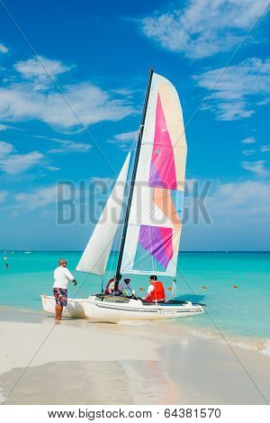 VARADERO,CUBA - APRIL 28,2014 : Tourists boarding a colorful sailing boat on a beautiful sunny day at the beach