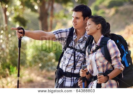 A man pointing something out to his girlfriend on the hiking trail