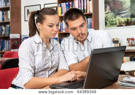 Students researching online at the library on computer