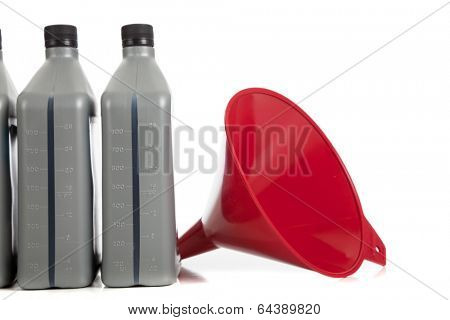 Three quarts of motor oil with a red funnel on a white background