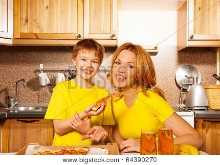 Smiling boy and his mother with pizza in kitchen
