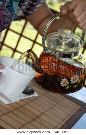 The Hand Pours Teapot In Cup Tea