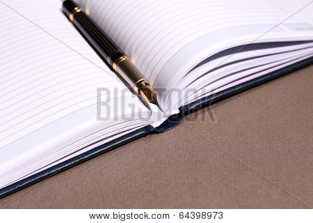 Pen on opened book on brown table, close up