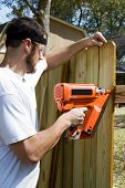 foto of guns  - Man wearing safety glasses uses a portable nail gun to attach wood pickets to the rail as he builds a privacy fence in the backyard - JPG