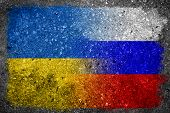 stock photo of merge  - Flags of Russia and Ukraine painted and merged on a concrete wall - JPG