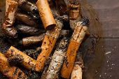 pic of anti-cancer  - Dirty cigarette butts in a glass ashtray on wooden table - JPG