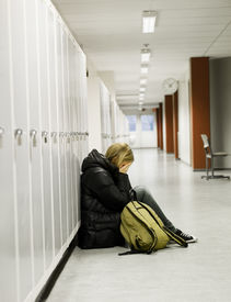 picture of school bullying  - Young woman crying by the lockers at school - JPG