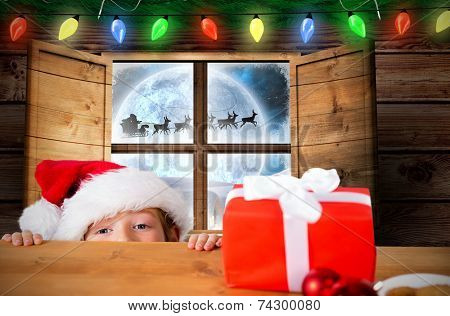 Festive boy peeking over table against santa delivery presents to village