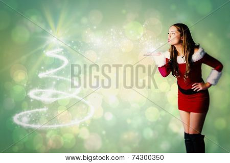 Sexy santa girl blowing a kiss against green abstract light spot design