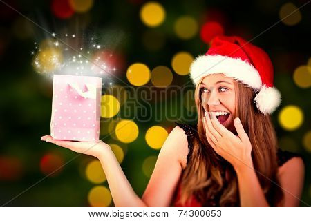 Festive blonde holding a gift bag against close up of christmas lights