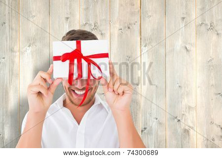 Man holding gift against pale wooden planks