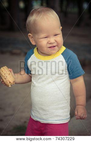 Cute caucasian baby eating corn