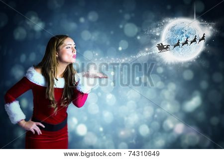 Sexy santa girl blowing a kiss against blue abstract light spot design