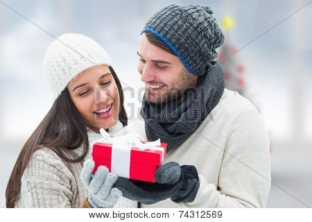 Winter couple holding gift against blurry christmas tree in room