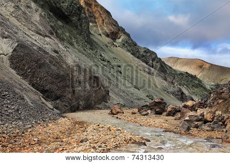 Creek in the gorge between the mountains of black volcanic ash.  National Park Landmannalaugar in Iceland