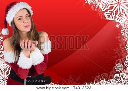 Sexy santa girl blowing over hands against christmas themed snow flake frame