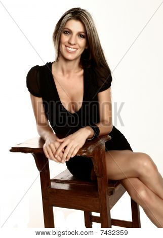 Smiling Blond Lady Sitting On A Chair