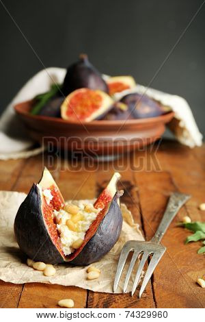 Ripe sweet fig with cottage cheese on wooden table, on dark background