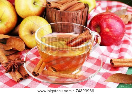 Composition of  apple cider with cinnamon sticks, fresh apples and autumn leaves on wooden table, on bright background