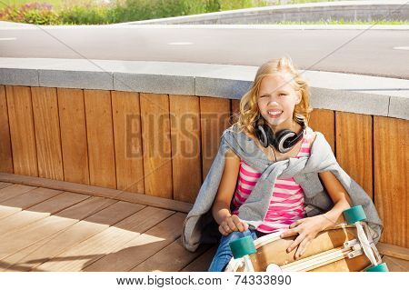 Blond girl wears sweatshirt over shoulders sitting