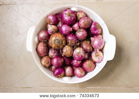 Closeup of an Old stock of onions kept in a storage bowl on an isolated background