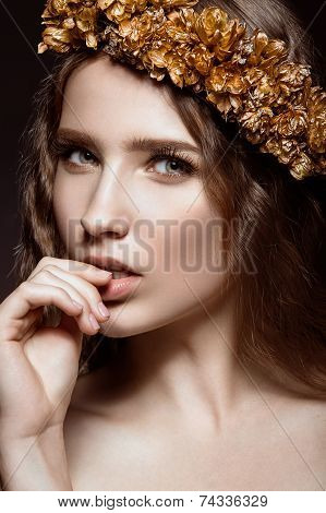 Beautiful girl with golden makeup and autumn wreath in her hair. Beauty face.