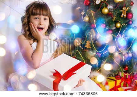 Beautiful Girl Near The Decorated Christmas Tree, Holds A White Gift