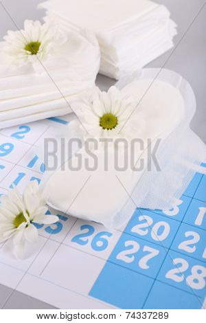 Sanitary pads, calendar and white flowers on light background