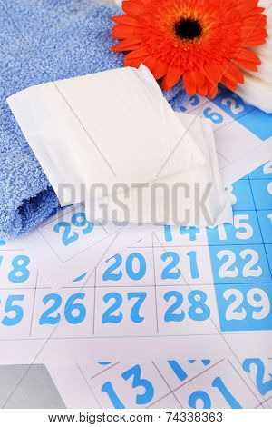 Sanitary pads, orange Gerber and towel on blue calendar background