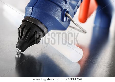 Dark blue glue gun and silicone stick on light background
