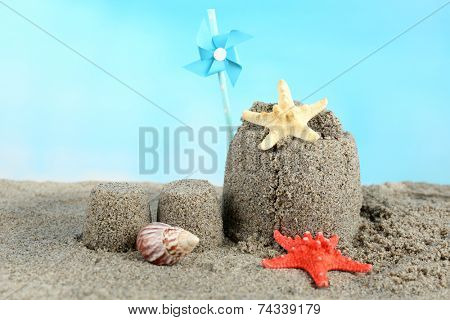 Sandcastle with starfish on sandy beach