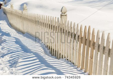 A wooden picket fence covered in deep snow.