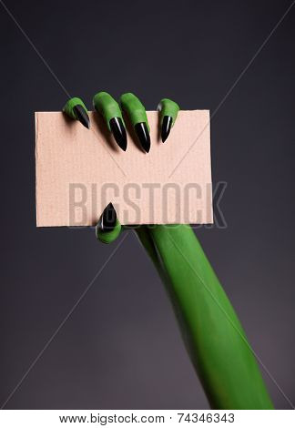 Green skin hand with sharp nails holding empty piece of cardboard, Halloween theme
