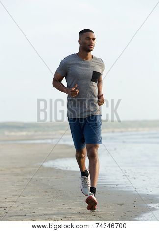 Young Black Man Running On Beach