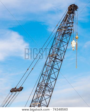 The Hoisting Crane With Pulley And Hook In Construction Site Against Blue Sky Background.