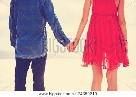 Young Happy Couple Holding Hands on the Sea Shore