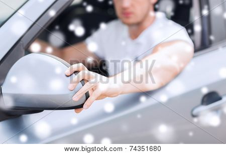 transportation, people and vehicle concept - close up of man adjusting car sideview mirror