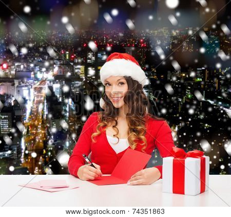christmas, holidays, celebration, greeting and people concept - smiling woman in santa helper hat with gift box writing letter or sending post card over snowy night city background