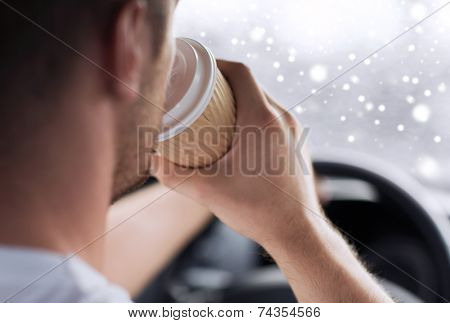 transportation, drinks, people and vehicle concept - close up of man drinking coffee while driving car