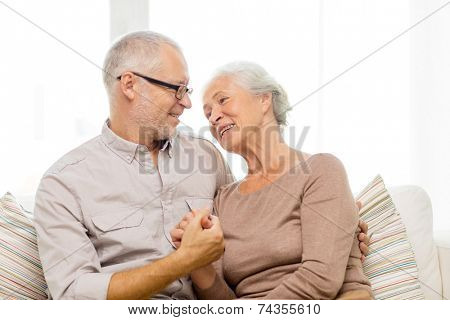family, relations, age and people concept - happy senior couple hugging on sofa at home