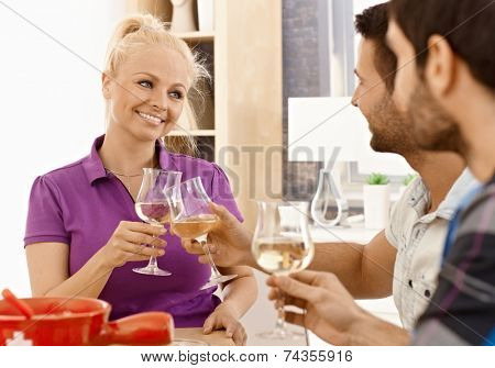 Happy woman clinking glasses with friends at dinner.