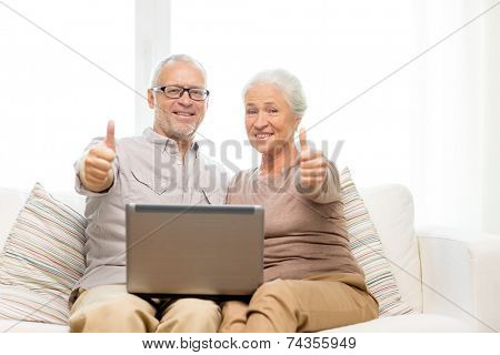 family, technology, gesture, age and people concept - happy senior couple with laptop computer showing thumbs up at home