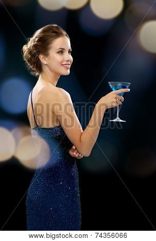 party, drinks, holidays, luxury and celebration concept - smiling woman in evening dress holding cocktail over night lights background