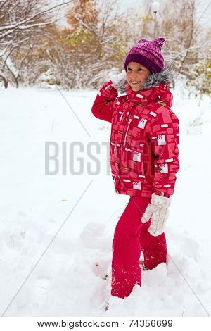 Happy Child Playing With Snowballs In Winter