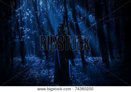 Young witch in night forest