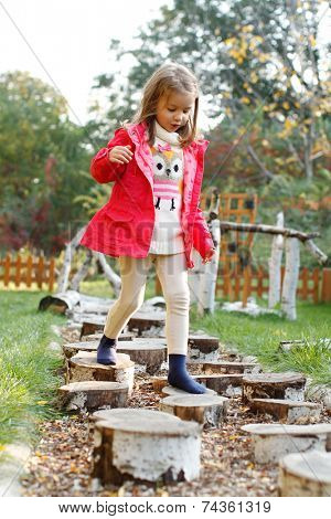 Five year old girl walking over pebbles. Sensory Discovery Walk. Sensory garden.