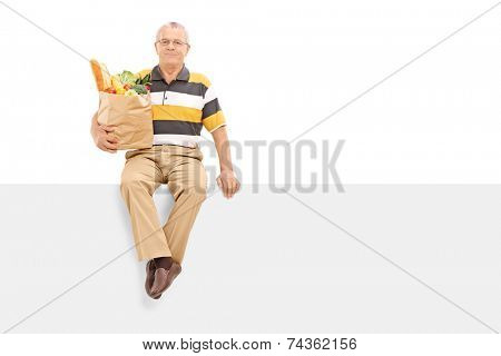 Senior holding bag with groceries seated on panel isolated on white background