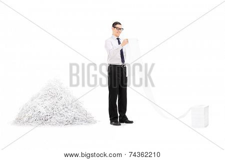 Man reading file in front of pile of shredded paper isolated on white background